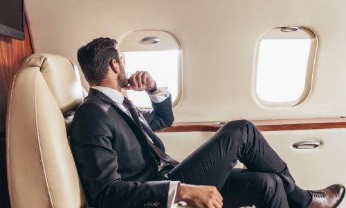 back view of businessman in suit looking through window in private plane